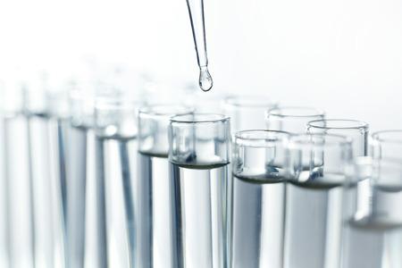 Pipety laboratoryjne z kropli cieczy ponad probówki szklane w laboratorium badawcze nauki