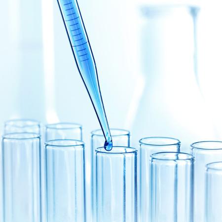 Pipeta con gota de líquido en tubos de ensayo de vidrio en un laboratorio de investigación en ciencias