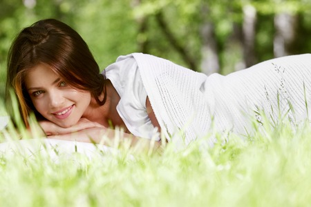 Young beautiful woman waking up on grass outdoors photo