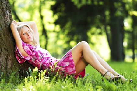 under tree: Beautiful Woman sitting under tree in spring park Stock Photo