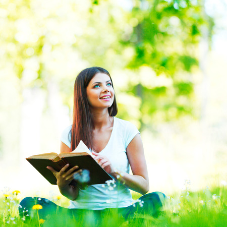 Young beautiful woman with book resting on fresh green grass with flowers photo