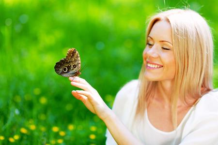 femme papillon: Belle femme blonde jouant avec le papillon dans un parc de printemps