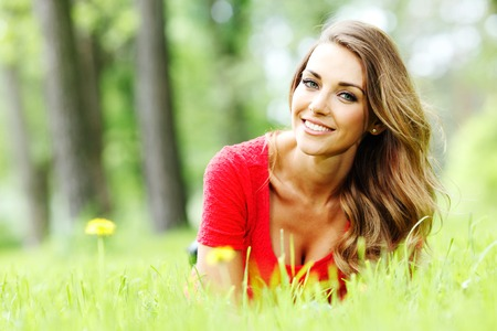 lying on grass: beautiful young woman in red dress lying on grass