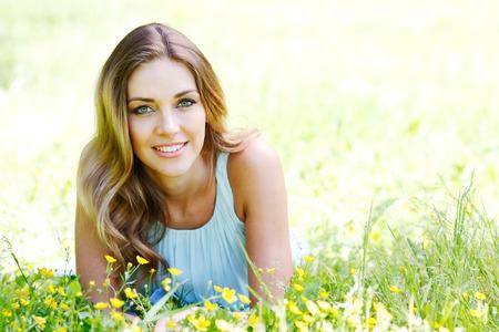 s úsměvem: krásná mladá žena v modrých šatech, ležící na trávě