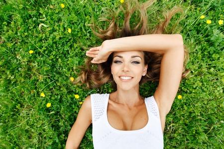 grass beautiful: beautiful young woman in white dress lying on grass Stock Photo
