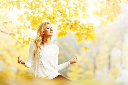 ロータス ヨガのポーズで秋の公園で座っている美しい若い女性 写真素材 - 43121849