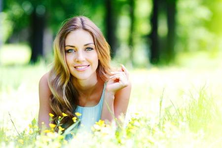 beautiful blonde: beautiful young woman in blue dress lying on grass