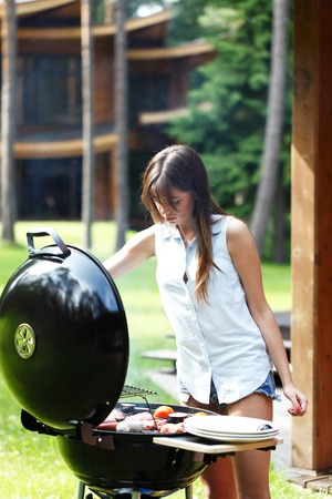 roast: woman cooks steak and sausages on grill Stock Photo