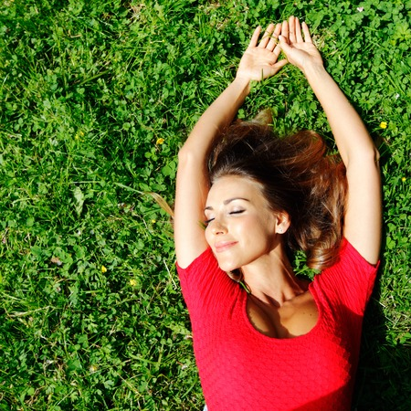 beautiful young woman in red dress lying on grass