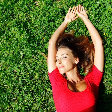 Schöne junge Frau im roten Kleid auf dem Rasen Standard-Bild - 43681189