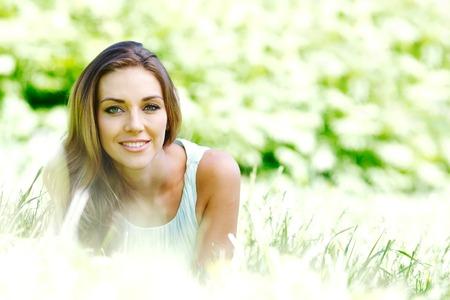 slim girl: beautiful young woman in blue dress lying on grass