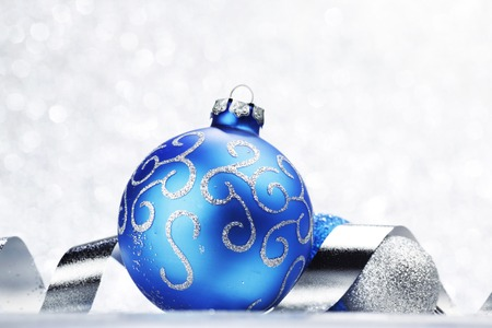 blue ball: Blue Christmas ball and ribbon on abstract glitter silver background
