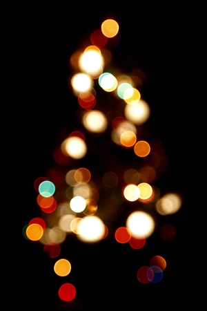 black tree: Bokeh silhouette of Christmas tree on black background
