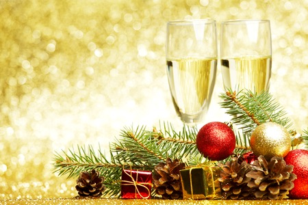 christmas decor: Champagne, fir tree, christmas decor and gifts on golden background