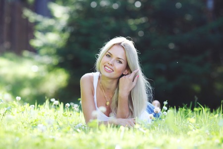 adult woman: young blond woman  lying on grass Stock Photo