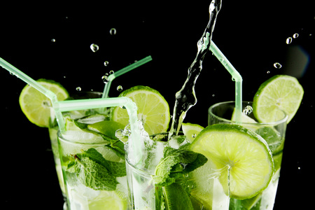 cocktail glasses: Pouring fresh mojito cocktail in glasses isolated on black background