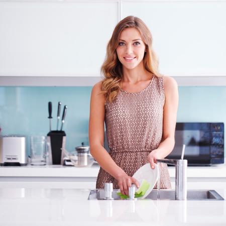lavar trastes: Ama de casa hermosa que hace platos jóvenes Foto de archivo