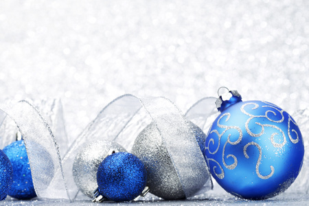 silver backgrounds: Beautiful Glitter christmas balls and ribbon close-up on shining background