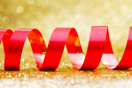 shiny gold: Curly red serpentine on shiny glitter gold background, holiday concept Stock Photo