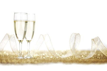 Two champagne glasses and golden shiny glitters isolated on white background Stockfoto