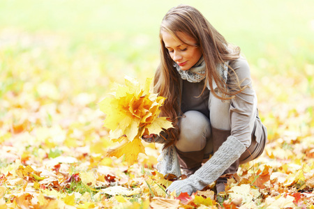pick up: Young woman picking bunch of autumn leaves