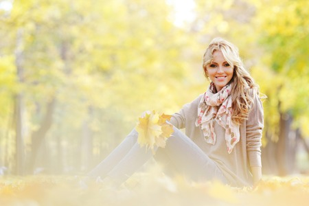 blonde females: Portrait of a cute smiling woman sitting on autumn leaves in park