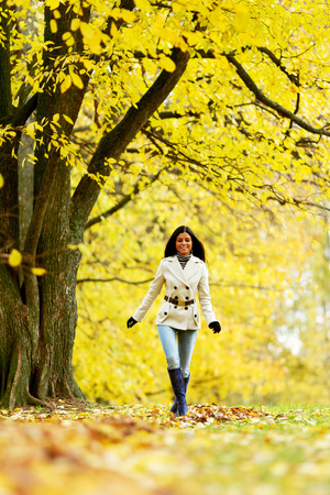 Smiling woman walking in park at autumn season photo
