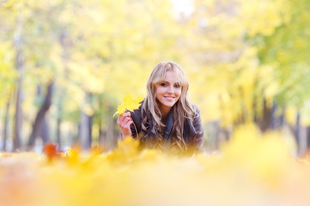 lying on leaves: Portrait of a cute smiling woman lying in autumn leaves in park