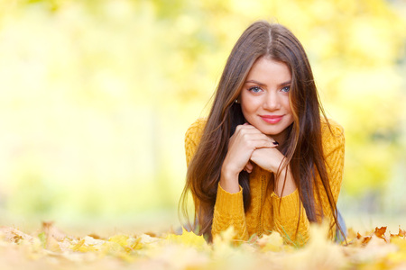 woman portrait: Portrait of a beautiful young brunette woman laying in the autumn park