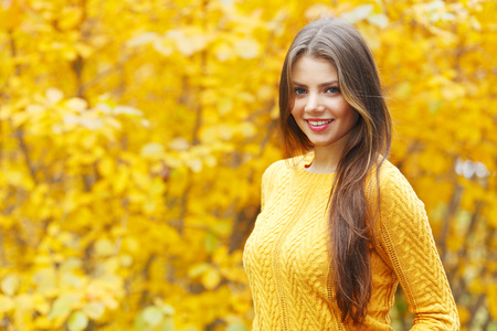 Young smiling brunette posing in autumn park on yellow trees background Stock Photo