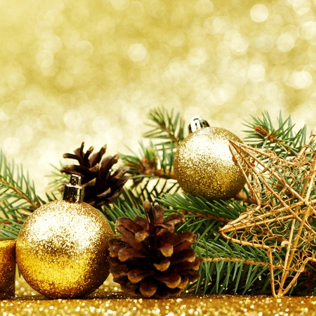 gold ornament: Christmas card with fir branch and decorations on golden gitter background