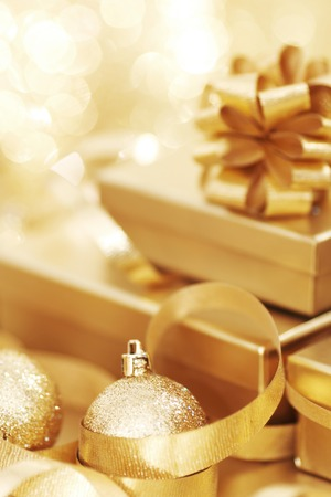 golden light: Golden christmas gift box and christmas balls on bokeh light background Stock Photo