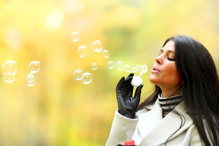 Young Woman Blowing Bubbles on autumn park background photo