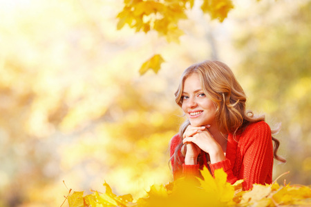 lying on leaves: Beautiful smiling woman lying in autumn maple leaves in park Stock Photo