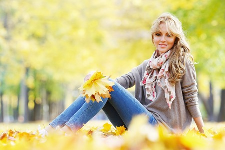 women sitting: Beautiful young woman sitting and holding bunch of fall leaves in autumn park Stock Photo