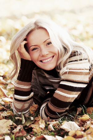 woman laying down: Beautiful smiling woman laying down on dry autumn leaves