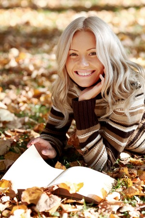 fall of the leaves: Woman lying on fallen leaves in autumn park and reading a book