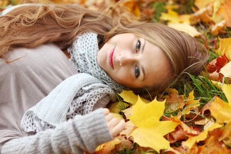 woman laying down: Beautiful dreamy woman laying down on dry autumn leaves