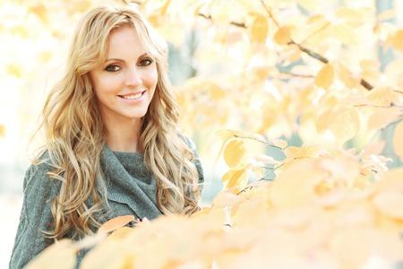 blonde woman: Portrait of young woman in beautiful autumn park