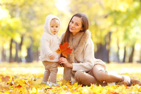 september 2: Mother and child having fun in autumn park among yellow leaves