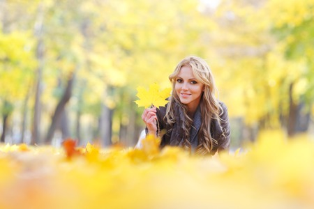 blonde females: Portrait of a cute smiling woman lying in autumn leaves in park