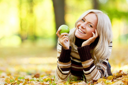 woman diet: Beautiful woman with green apple in autumn park