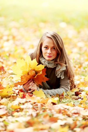 woman laying down: Young woman laying down on the ground in autumn park