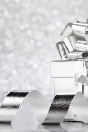 silver backgrounds: Decorative silver box with holiday gift on shiny glitter background