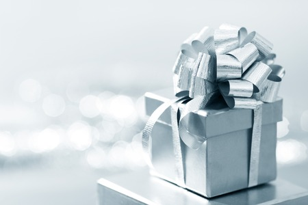 Holiday gift in silver box decorated with ribbon and bow