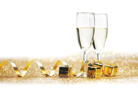 Two champagne glass on golden christmas glitter bokeh background
