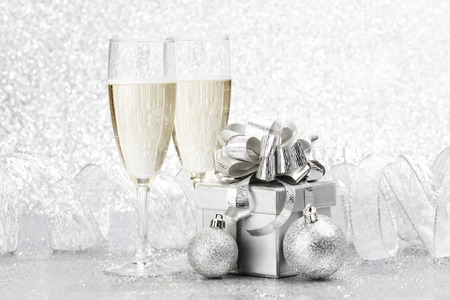 wine glasses: Two champagne glasses and christmas decoration on silver bokeh background Stock Photo