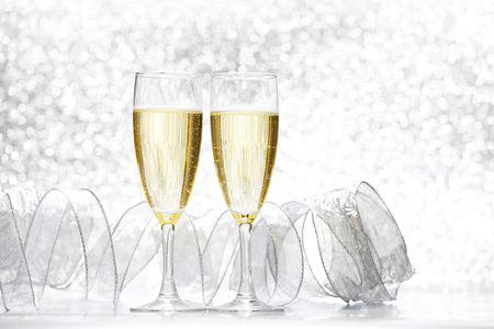 silver flute: Glasses of champagne and silver ribbons on glitter background