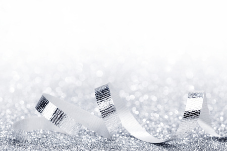 decoration: Shiny silver ribbon curls on silver glitters with white copy space Stock Photo
