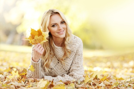 woman beautiful: Portrait of beautiful woman laying in autumn park with maple leaves